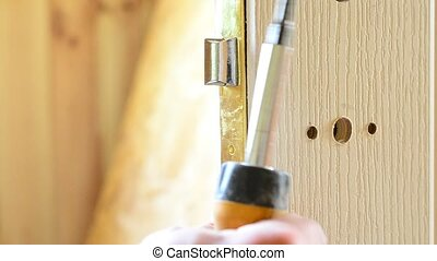 Mounting a door lock. Inserting mortise lock into pocket -...