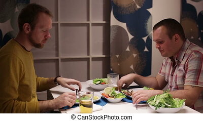 Men have dinner at the table, drinking and talking