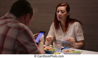Woman and man having dinner at the table.