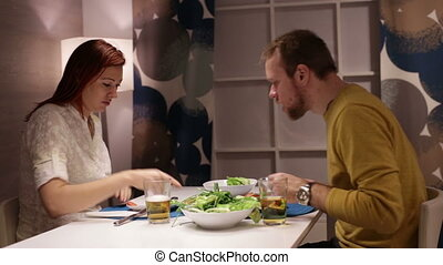 Woman and man having dinner and talking at table.