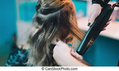 Hairdresser straightens the hair of the client - Hairdresser...
