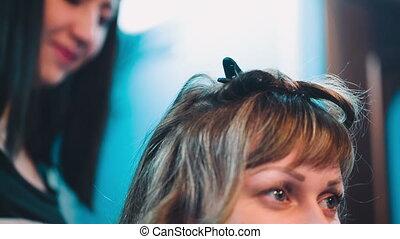 Hairdresser straightens client hair.