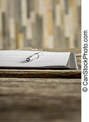 Low angle view of ink pen lying on a document in folder...