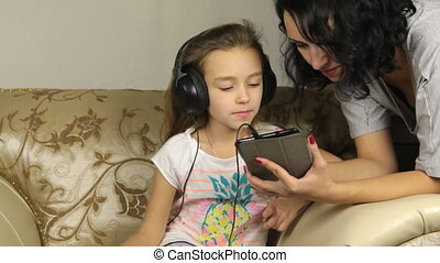 Mom helping her daughter play on the tablet, music, cartoon, internet.