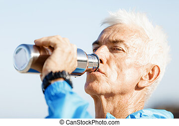Man drinking from a sports bottle - Handsome healthy man in...