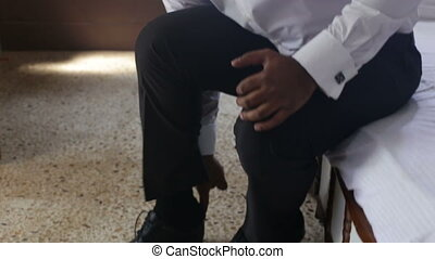 man in white wedding shirt puts on black shoes ties shoe-laces