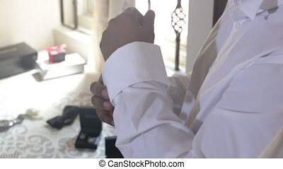 man buttons up white wedding shirt cuffs with cufflinks