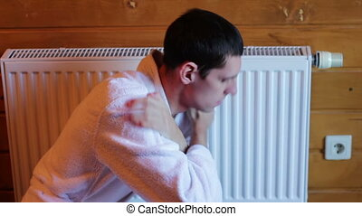 Man freezes near the radiator in the house - Man in home...