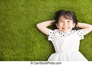 happy Little  girl resting on the grass
