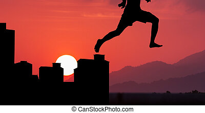 silhouette of the young man jumpping from town to nature at...