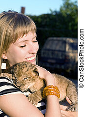 young woman - Portrait of young woman playing with lion cub