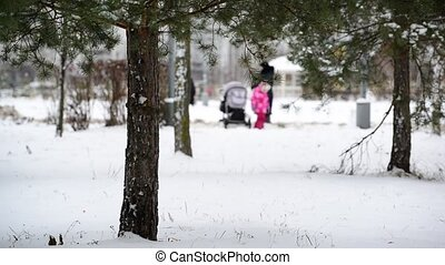 woman with a child in the park in winter. Out of focus