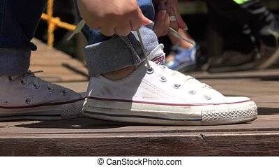 Female Tying White Sneakers