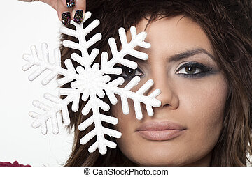 Girl holding snowflake close her face