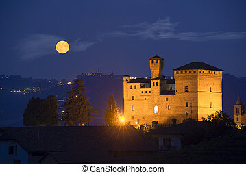 Castle of Grinzane Cavour in nocturnal with a full moon -...