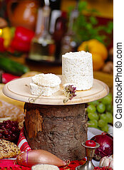 pieces of cheese on a knife board on a rustic background,...