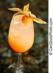 glass filled with orange colored cocktail - close-up of a...