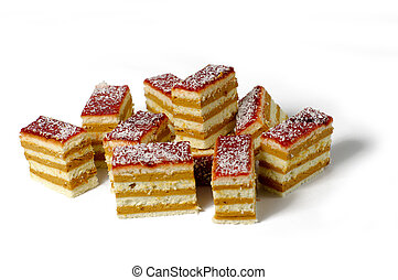 close-up of ten pieces of delicious layered sponge and custard cake, with red frosting and coconut sprinkles ontop, on a white background