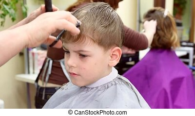 Child gets a haircut in tonsorial