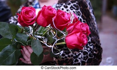 a bouquet of red roses in the hands of women