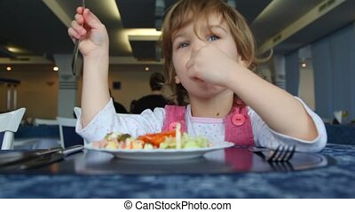 Small girl eats salad in caf