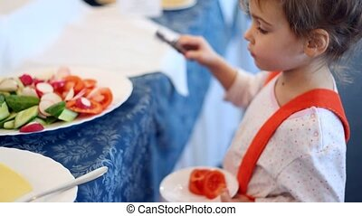 Small girl places piece of the tomato in plate