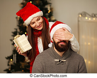 Happy girl gives her boyfriend a Christmas present, covering...