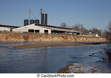 cattle ranch buildings on river shore - industrial barn and...