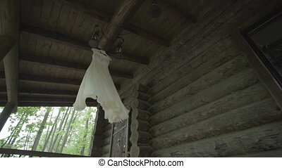 white wedding dress hanging on a wooden house