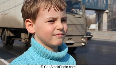 boy on road peers into distance