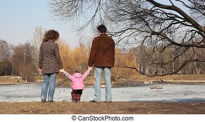 Girl with parent looks at pond