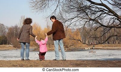 Girl jumps keeping hands of the parents