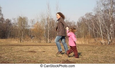 Mother and girl merrily play on glade