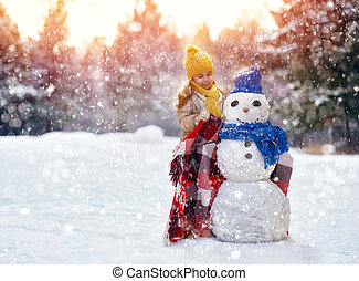 girl playing with a snowman - happy child girl plaing with a...
