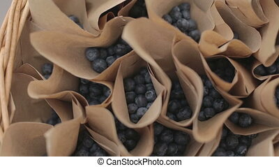 A brown paper bag full of picked blueberries - A brown paper...