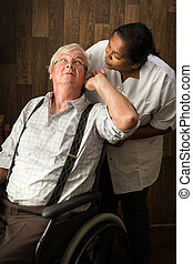 Hearing problems - Nurse in a home talking loudly to a...