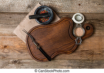 Cutting board, seasonings and meat fork on wooden...