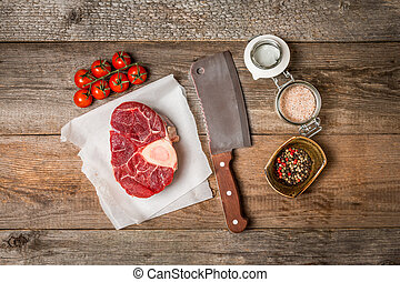Raw fresh cross cut veal shank and meat cleaver for making...