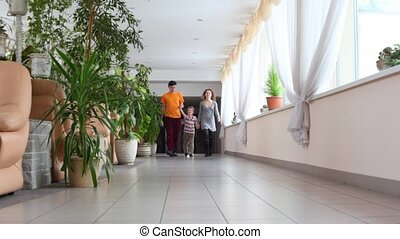 Family three go on corridor
