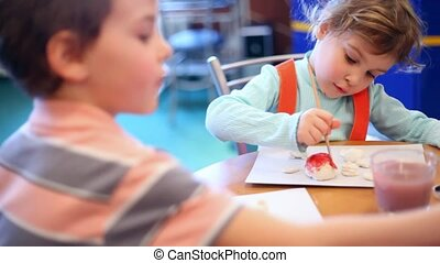 Two children draw paint
