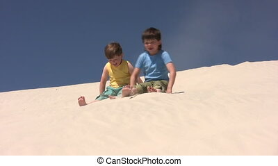 Kids scramble down by the sand