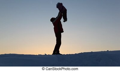 Silhouette father tosses child upwards