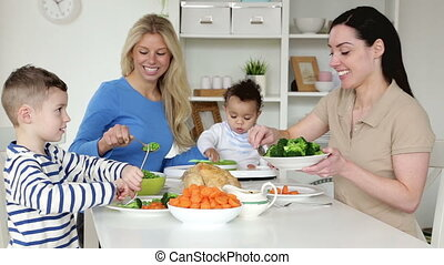 Female couple having dinner with their children - Same sex...