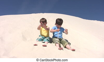 Boys strew the sand on the legs