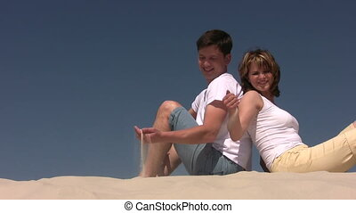 Couple plays with the sand