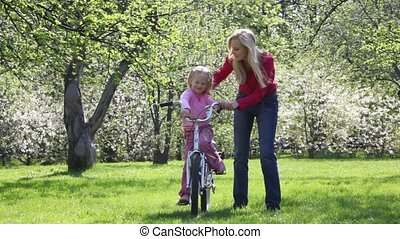 girl learns sit on bicycle