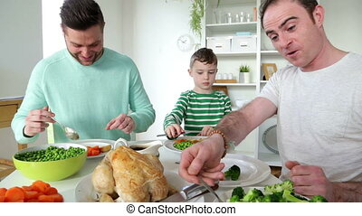 Male couple having dinner with son - male couple having...
