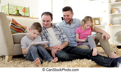 Male couple helping their children with homework - Male...