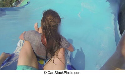 Fun with girl on water slide in aqua park