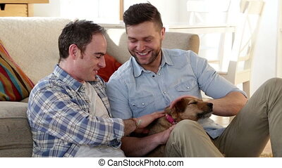 Male couple talking and petting their dog